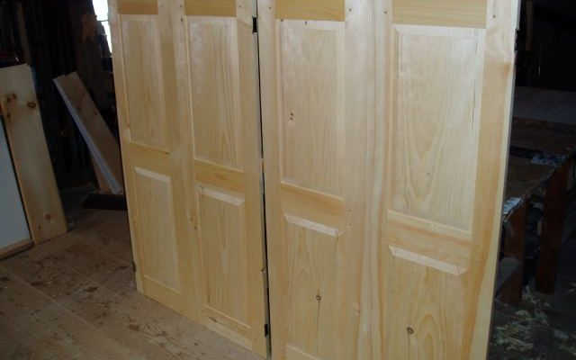 Pair of custom doors for a low height storage area that makes use of the extra unused space under the roof line on an upper story of a house.
