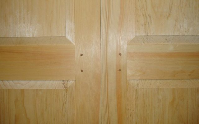 Mid-rail detail on a pair of custom doors for a low height storage area that makes use of the extra unused space under the roof line on an upper story of a house.