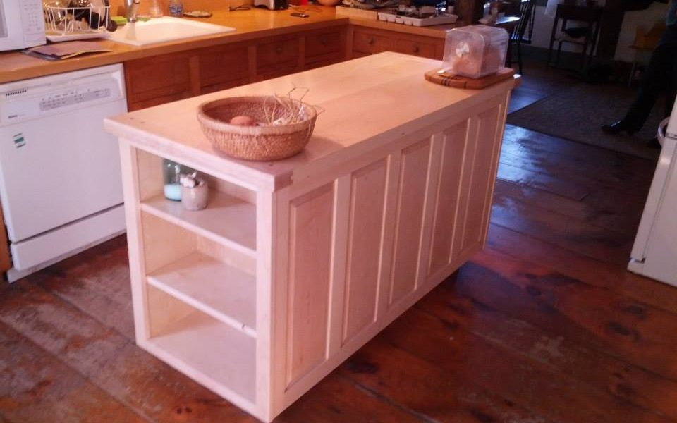 The raised panels along the back of this maple island hide a section of cookbook shelves accessible from the end.