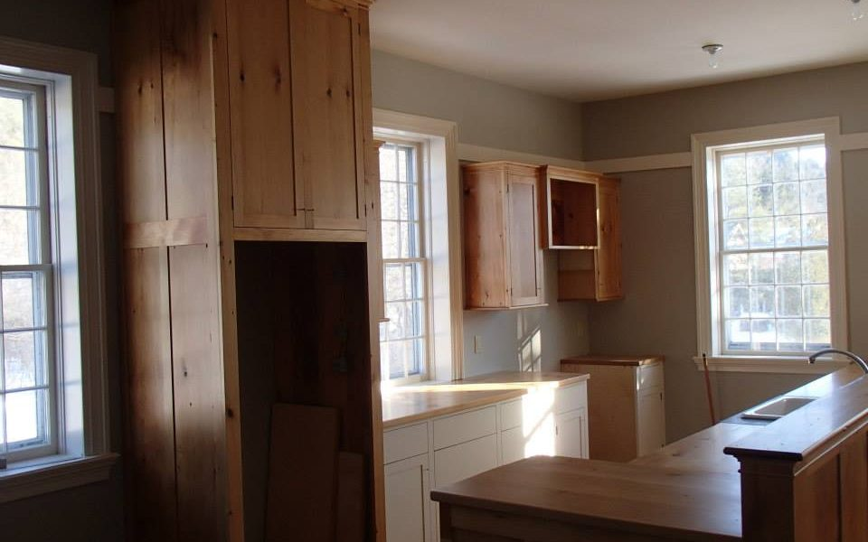 Wide pine planks salvaged from the closets of a historic in became rich, warm cabinetry for the upstairs living space.