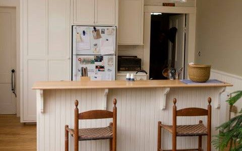 This simple white kitchen provides storage space in a former schoolhouse converted to a residence.