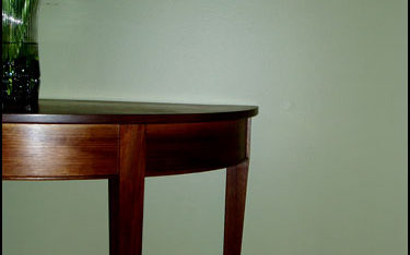 Walnut demilune table with curved and tapered legs.