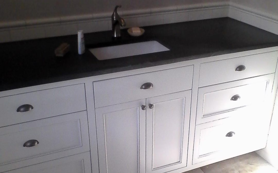 A large white painted vanity with slab and beaded panel drawer fronts and center tip out tray.