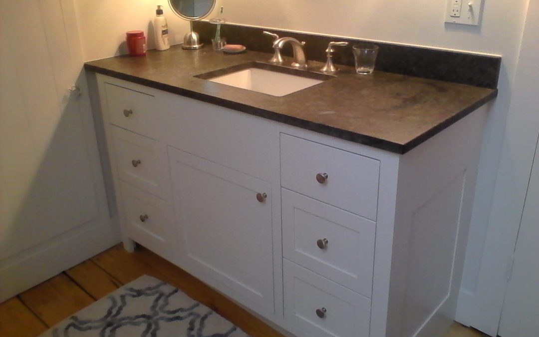 Painted bathroom vanity with slab and paneled drawer fronts.