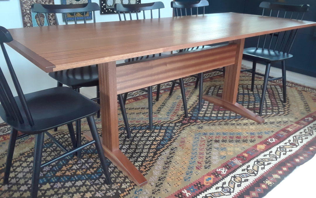 Clear finished dining room trestle table in sapele mahogany.